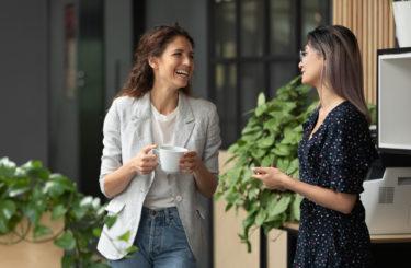 Happy female colleagues talking laughing during break in work space