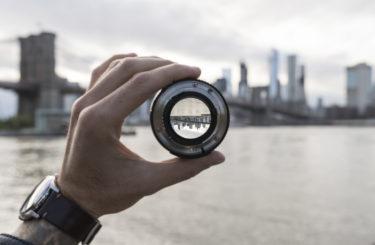Hand holding a lens against New York City skyline