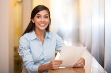 Smiling Pretty Woman Holding Document in Cafe