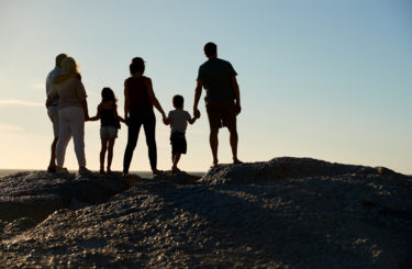 Three generation family on a beach holding hands, admiring view, full length, silhouette, back view