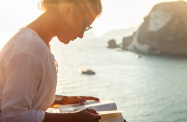 Young woman reading book at sunset in front of the sea on Ponza island coast, sitting on a wall with view of the ocean.