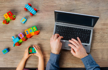 Close up of kids hands playing with colorful blocks near father working on the laptop