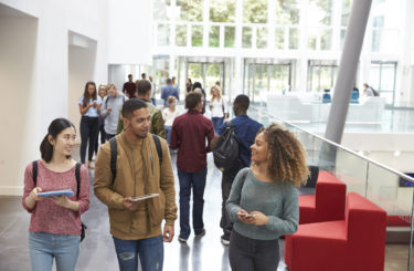 Students holding tablets and phone talk in university lobby