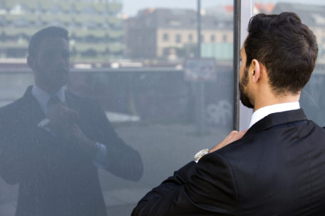 businessman standing outside and looking at his reflection in window