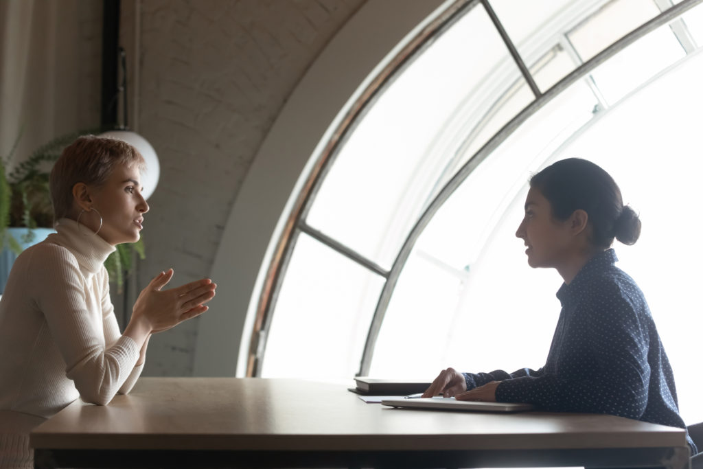 Confident Indian hr manager holding interview with candidate in office