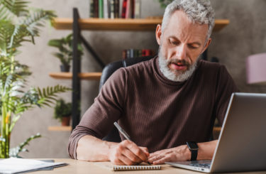 Middle aged businessman in casual clothes making notes in notepad while sitting in his office