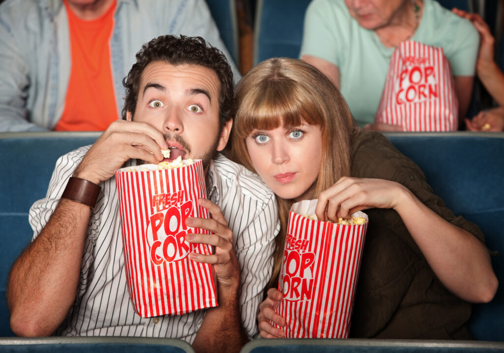A couple in an audience shows suspense and intrigue